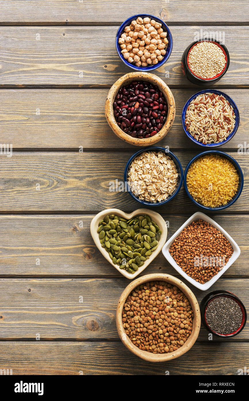 A set of various superfoods , whole grains,beans, seeds, legumes in bowls on a wooden plank table. Top view, copy space Stock Photo