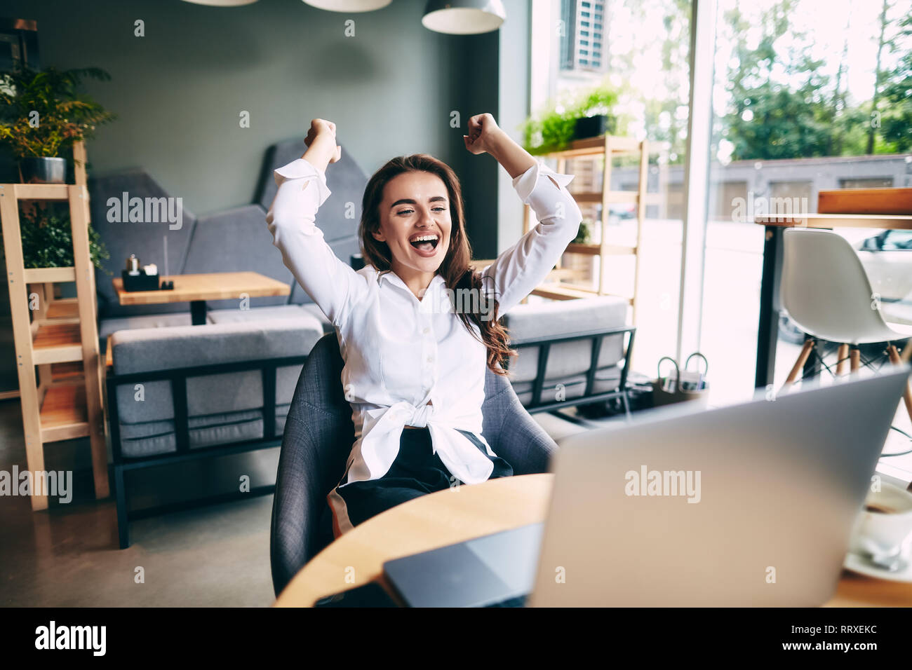 Attractive girl in white shirt working in cafe with gray laptop,  freelance work in progress, work from home, excited, winner. - Stock Image
