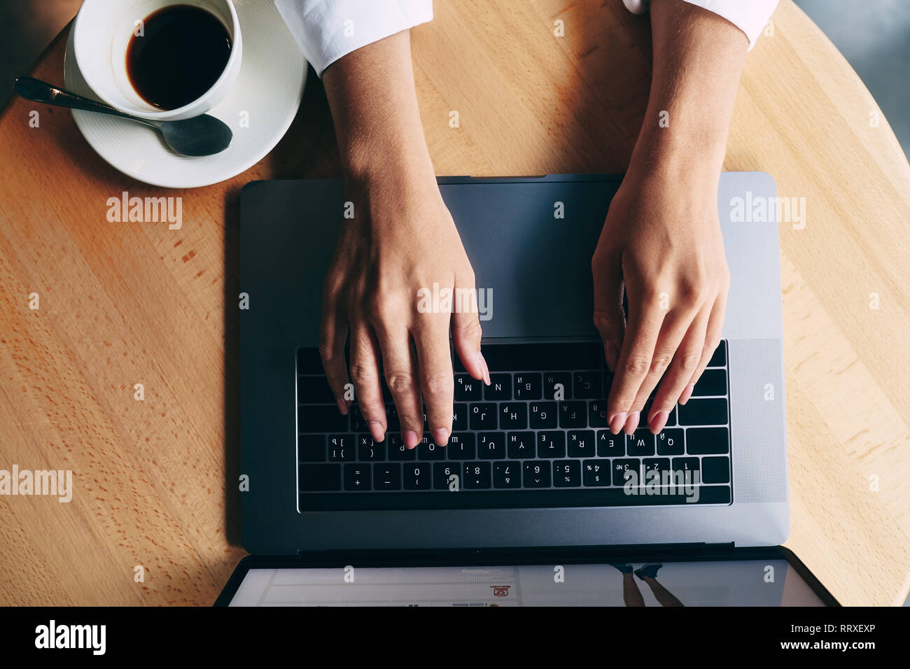 Gray laptop and coffee on table. Online shopping concept, freelance work in progress, close up portrait, working with laptop. - Stock Image