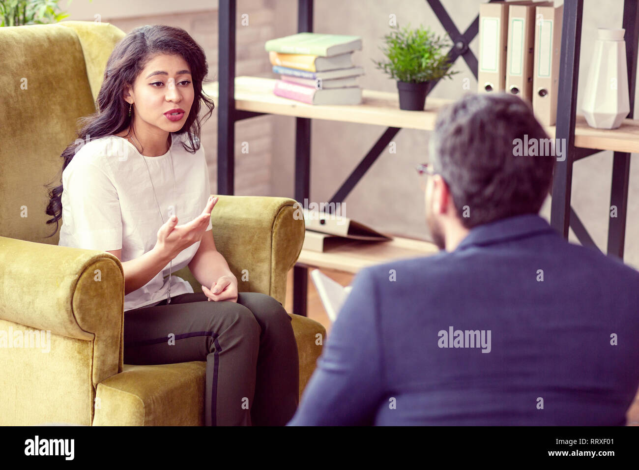 Beautiful nice woman talking to her personal therapist - Stock Image