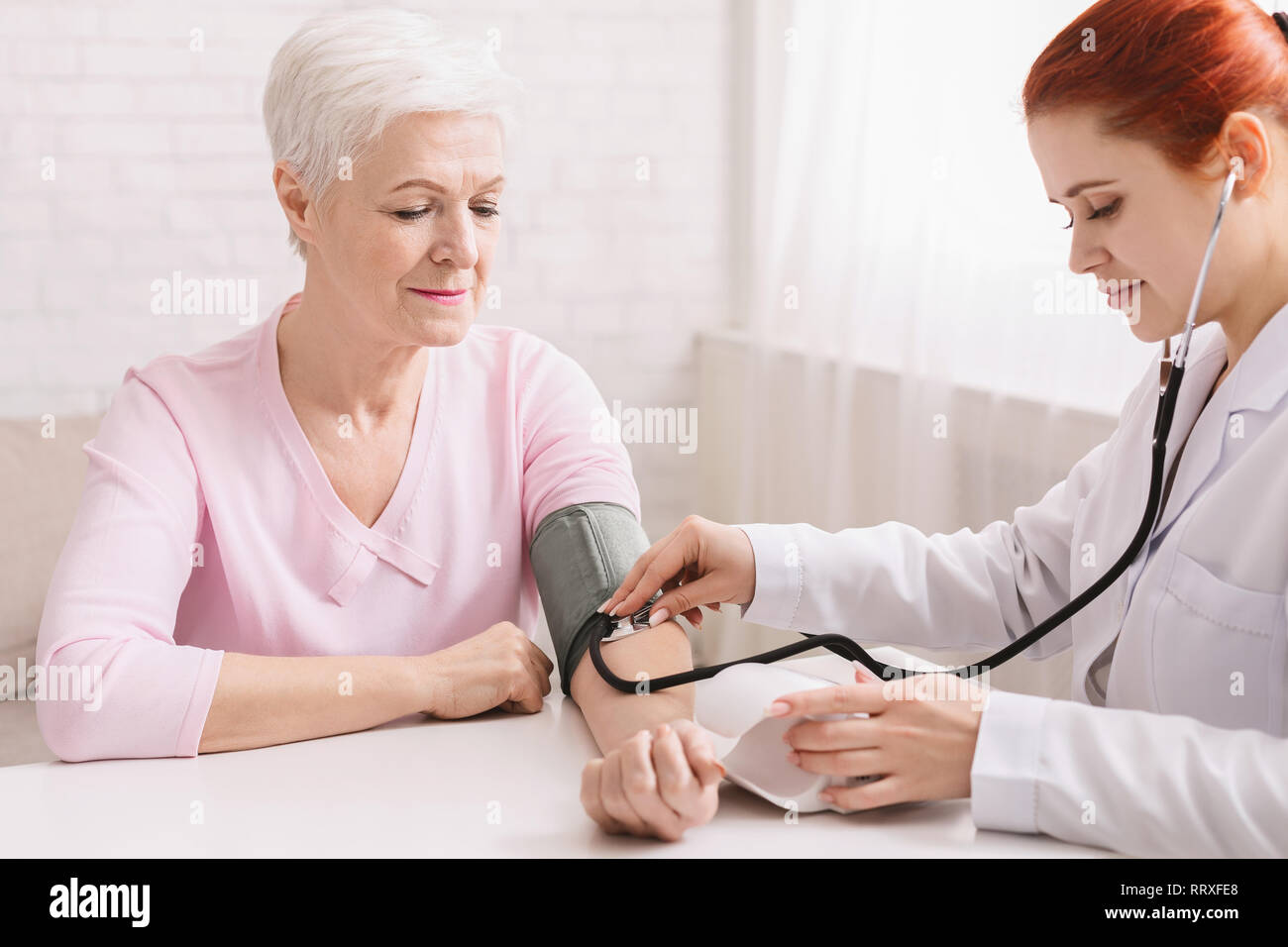 Doctor checking blood pressure of senior patient - Stock Image