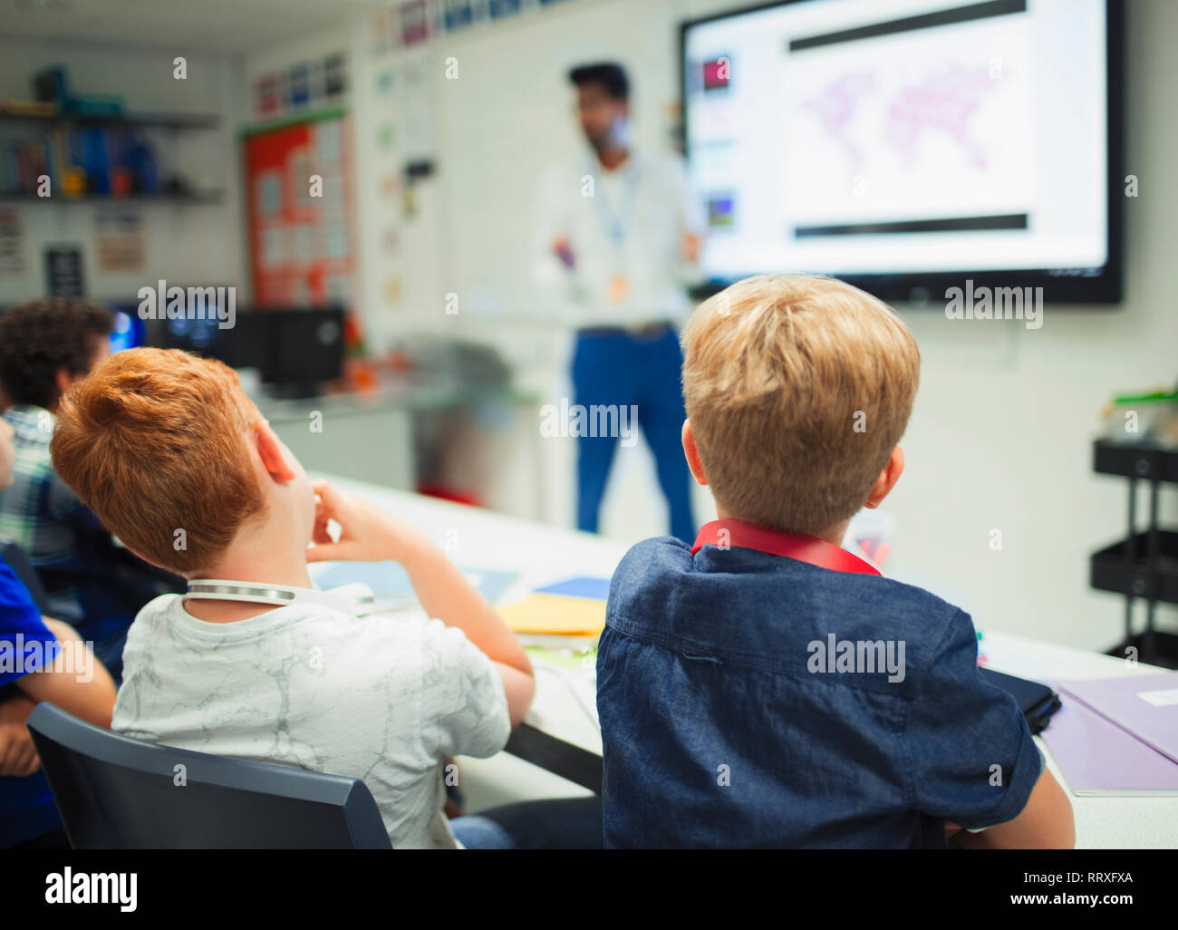 Junior high school boys watching teacher during lesson in classroom Stock Photo