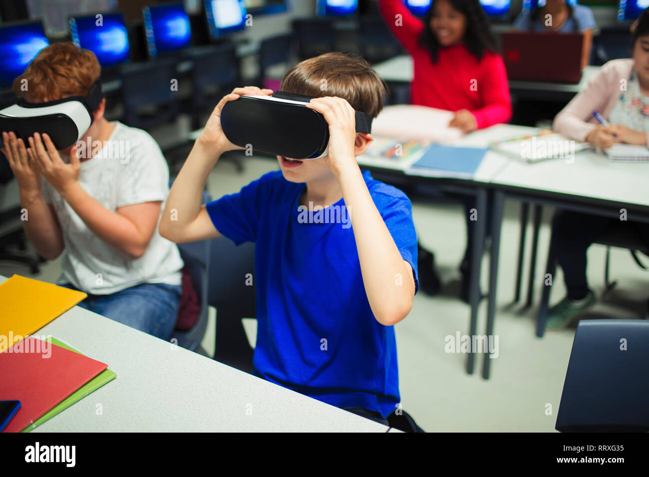 Junior high school boy students using virtual reality simulators in classroom Stock Photo