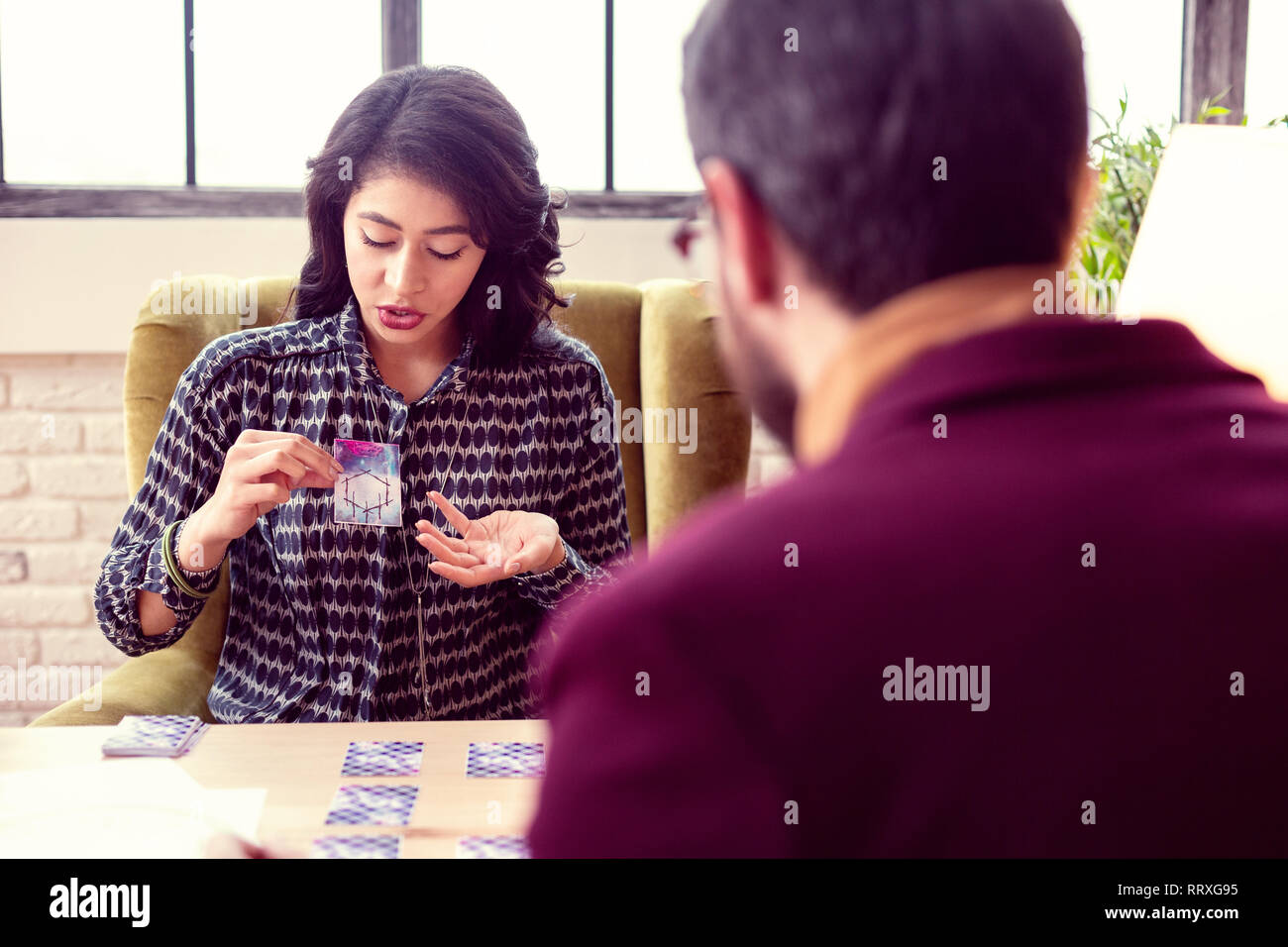 Nice dark haired woman explaining the meaning of a card - Stock Image