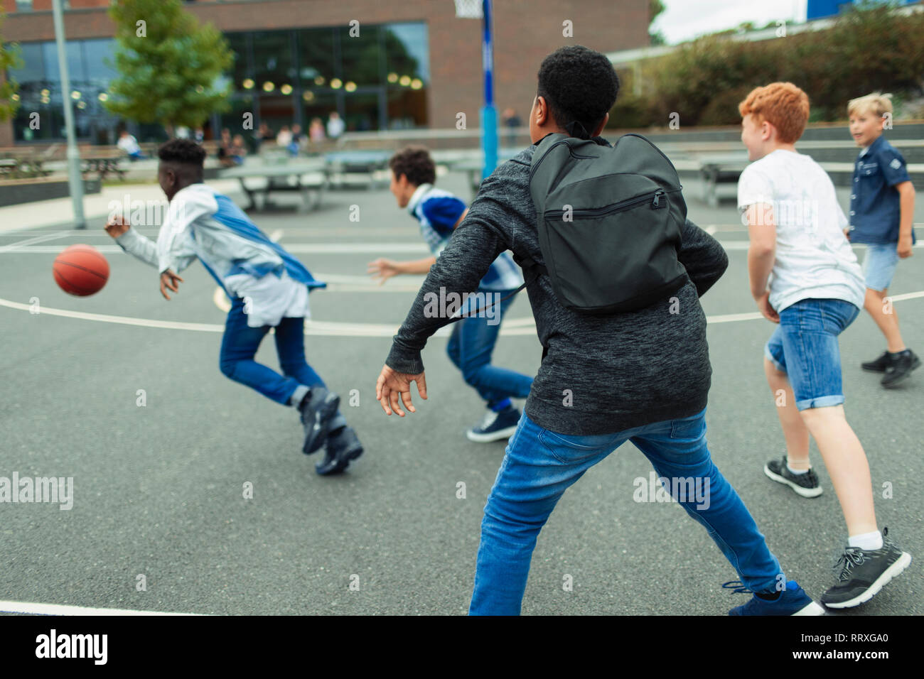 Junior high boy students playing basketball in schoolyard Stock Photo