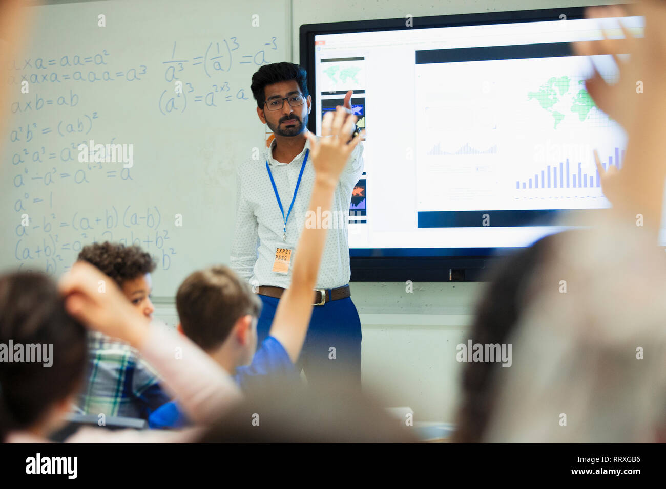 Teacher leading lesson, calling on students in classroom Stock Photo