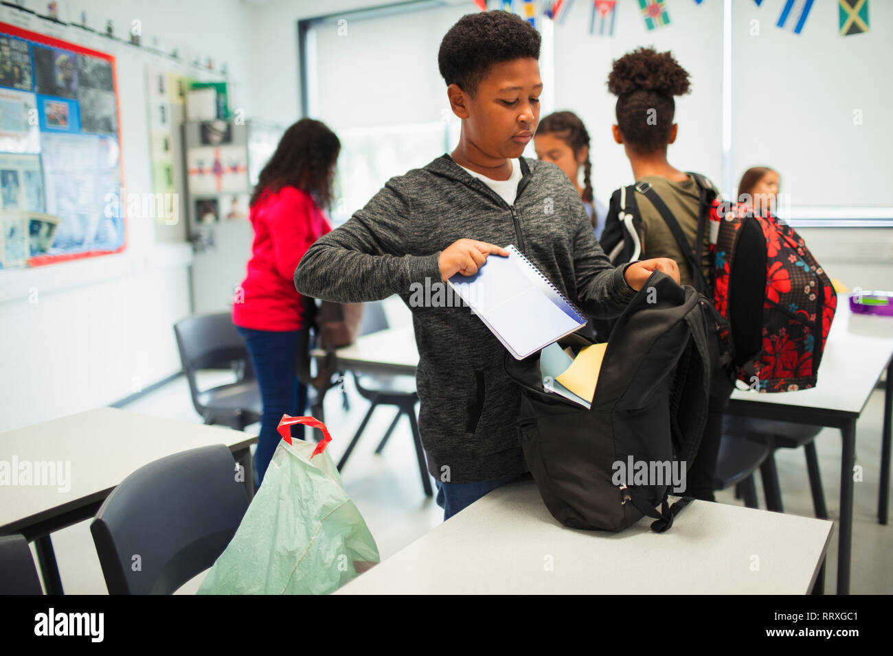 Junior high school boy placing notebook in backpack in classroom Stock Photo