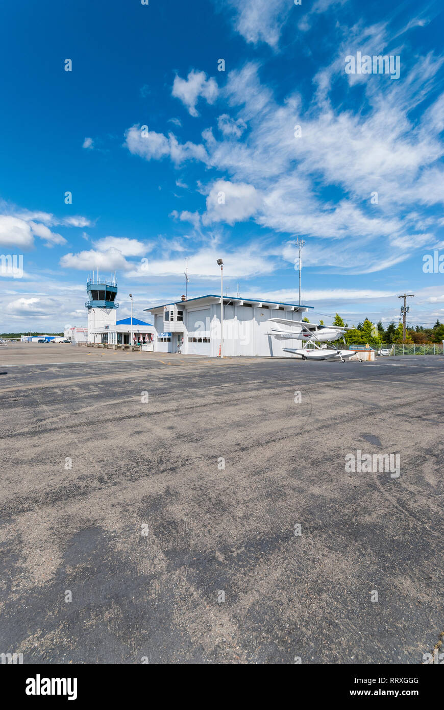 A high-wing amphibious aircraft sits in front of the control tower facility at the airport in Gig Harbor, Washington. - Stock Image