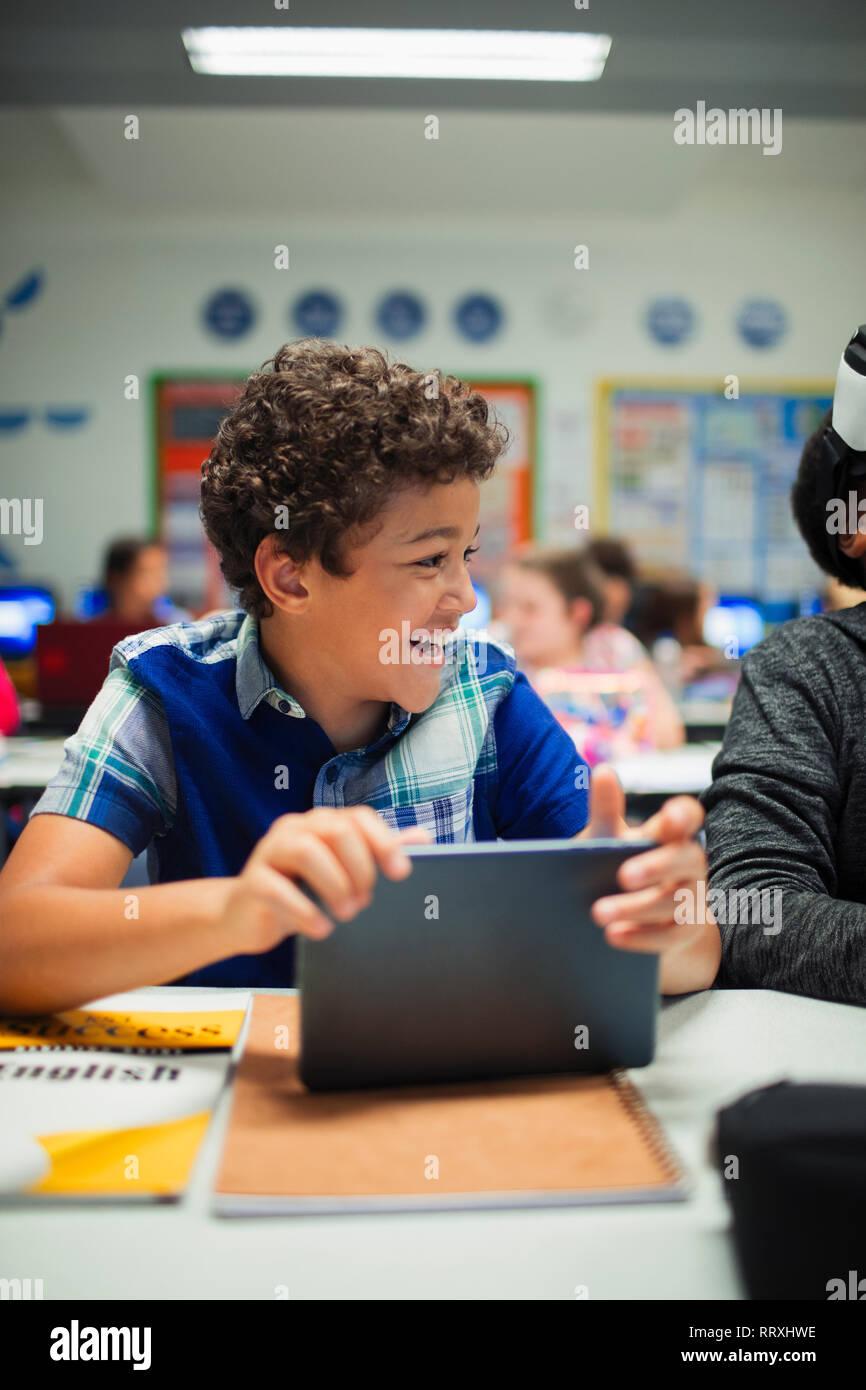 Happy elementary school boy using digital tablet in classroom Stock Photo