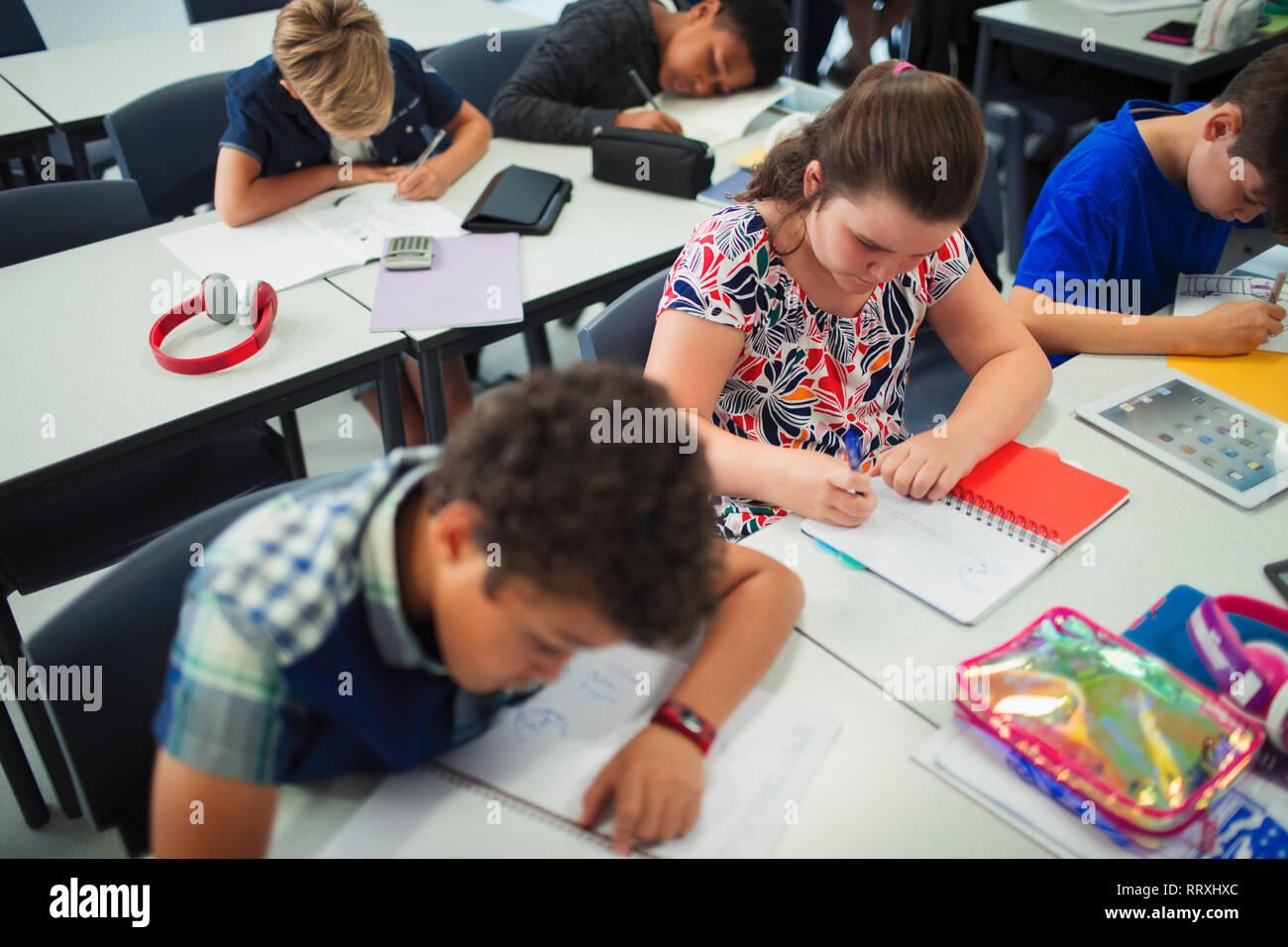 Junior high school students doing homework at desks in classroom Stock Photo