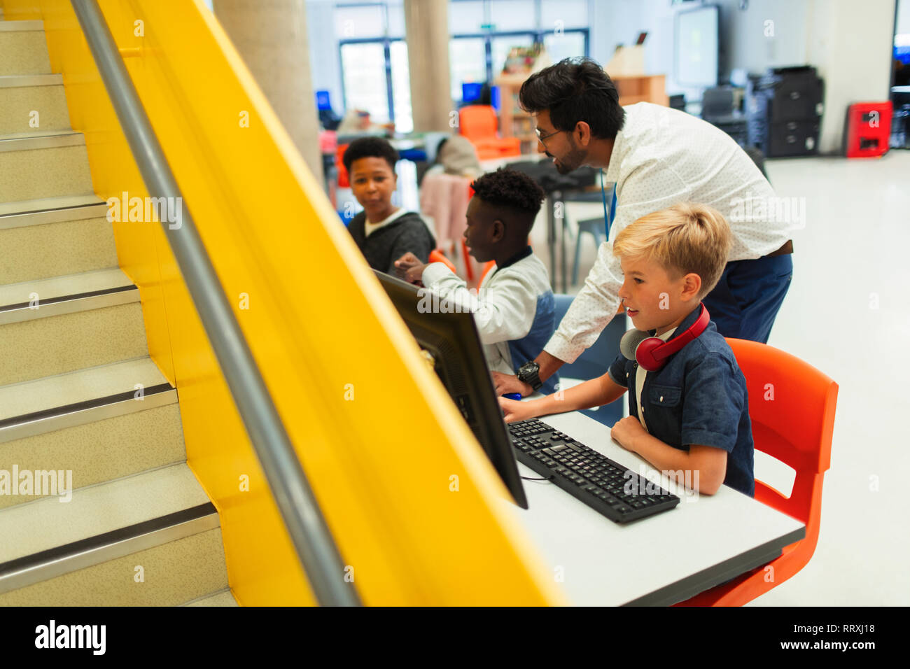 Teacher helping junior high students using computers in library Stock Photo