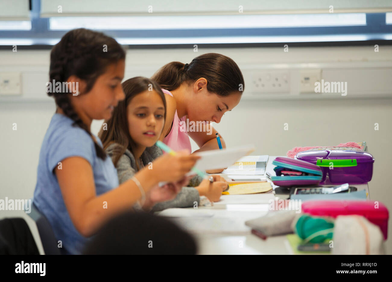 Junior high school girl students studying at desk in classroom Stock Photo
