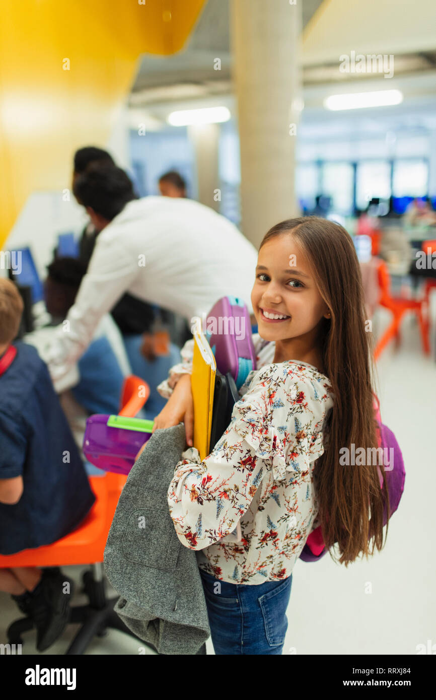 Portrait smiling, confident junior high girl student carrying books Stock Photo