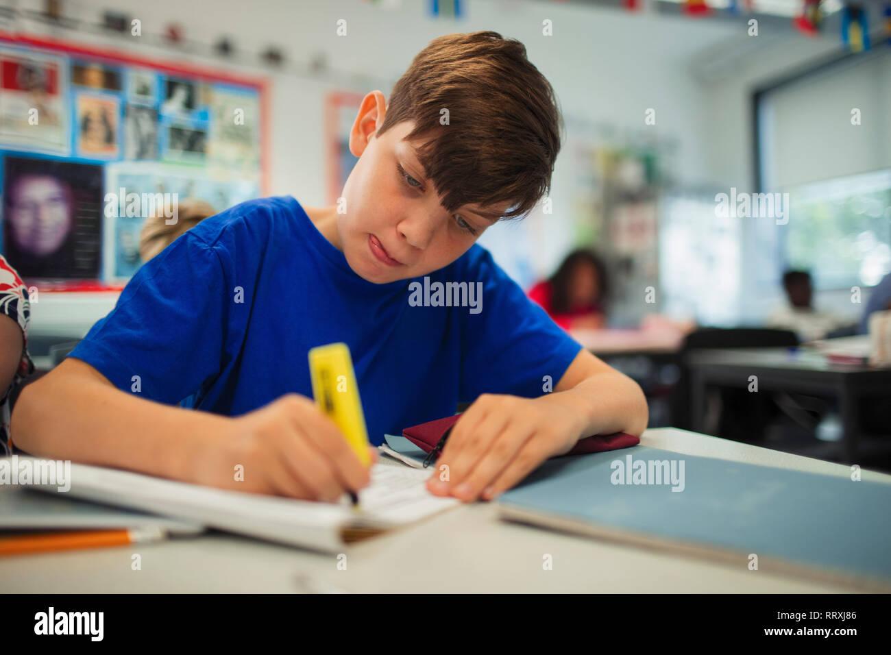 Focused junior high school boy student using highlighter, doing homework in classroom Stock Photo