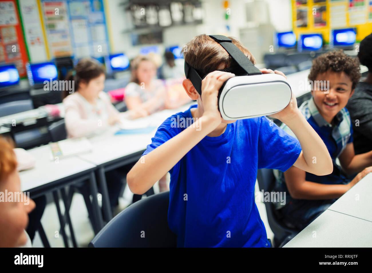 Junior high school boy student using virtual reality simulator glasses in classroom Stock Photo
