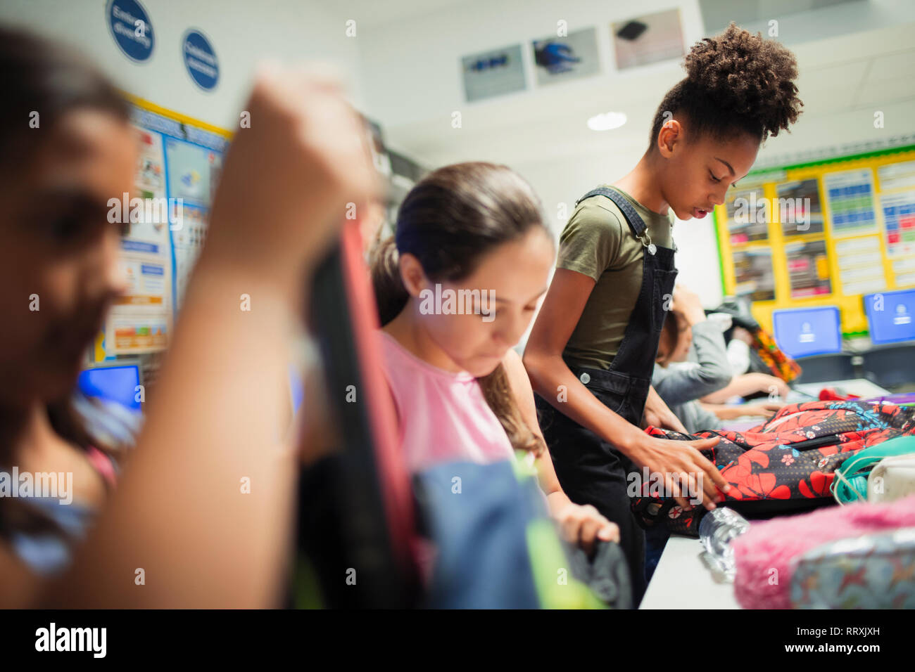 Junior high school girl students with backpacks in classroom Stock Photo