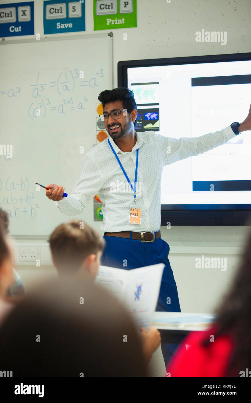 Smiling male teacher leading lesson in classroom Stock Photo