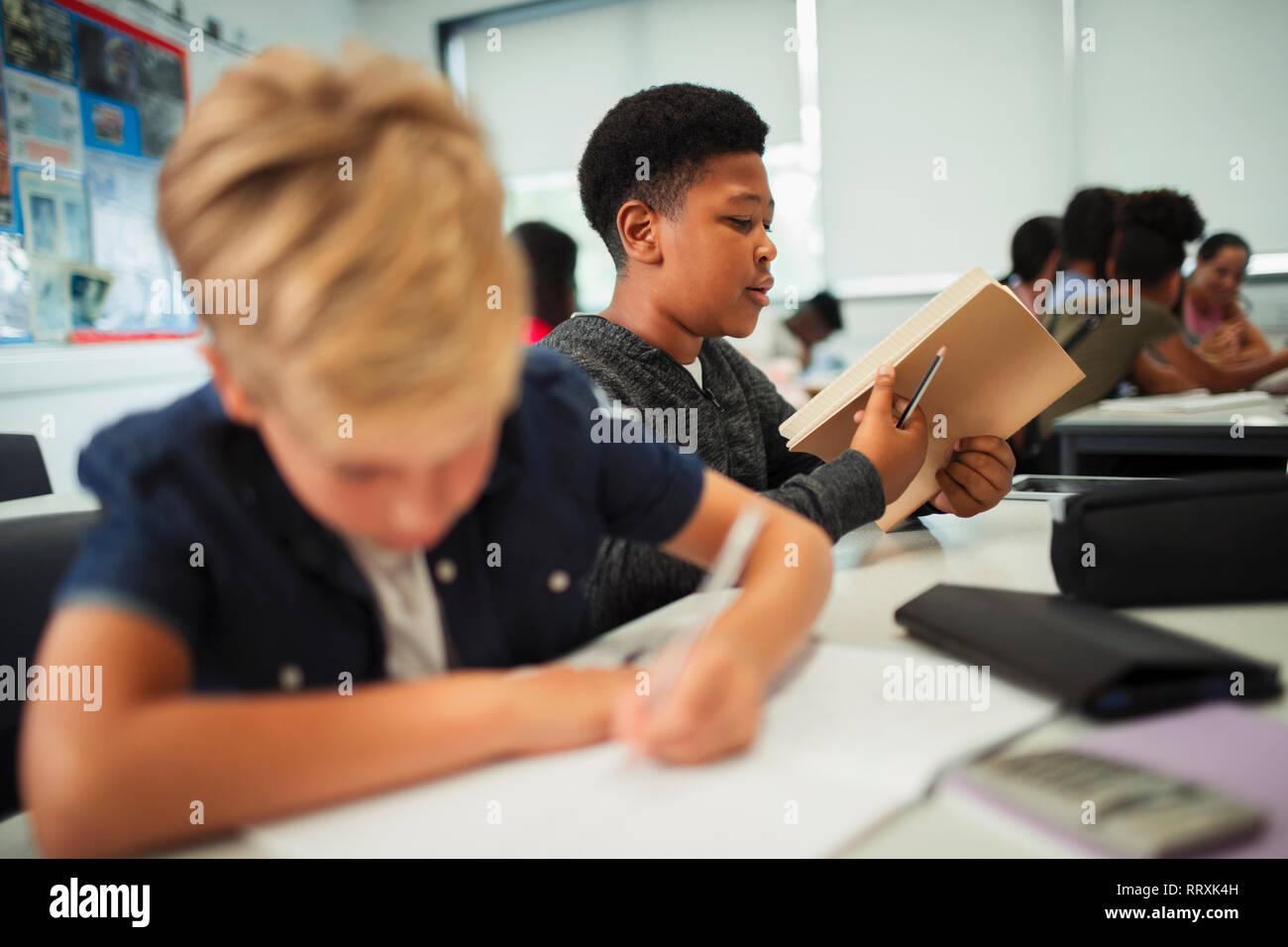 Junior high school boy opening notebook at desk in classroom Stock Photo