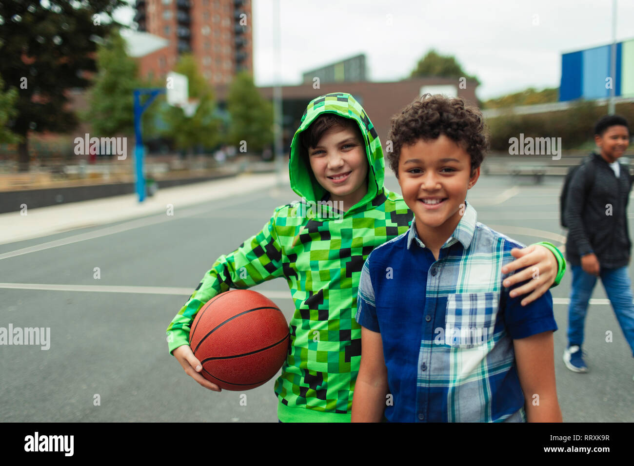 Portrait happy junior high boy friends playing basketball in schoolyard Stock Photo