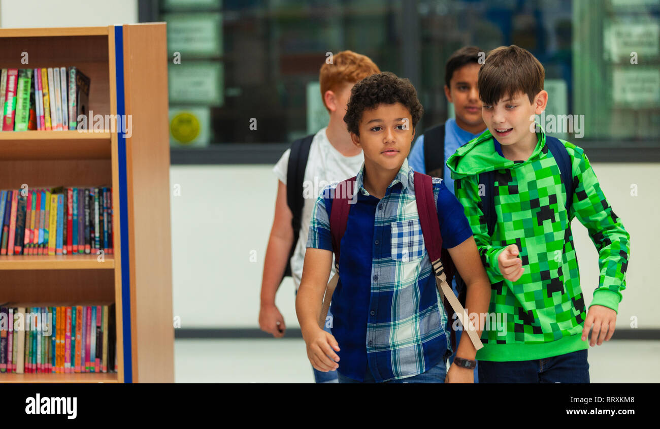 Junior high boy students walking in library Stock Photo