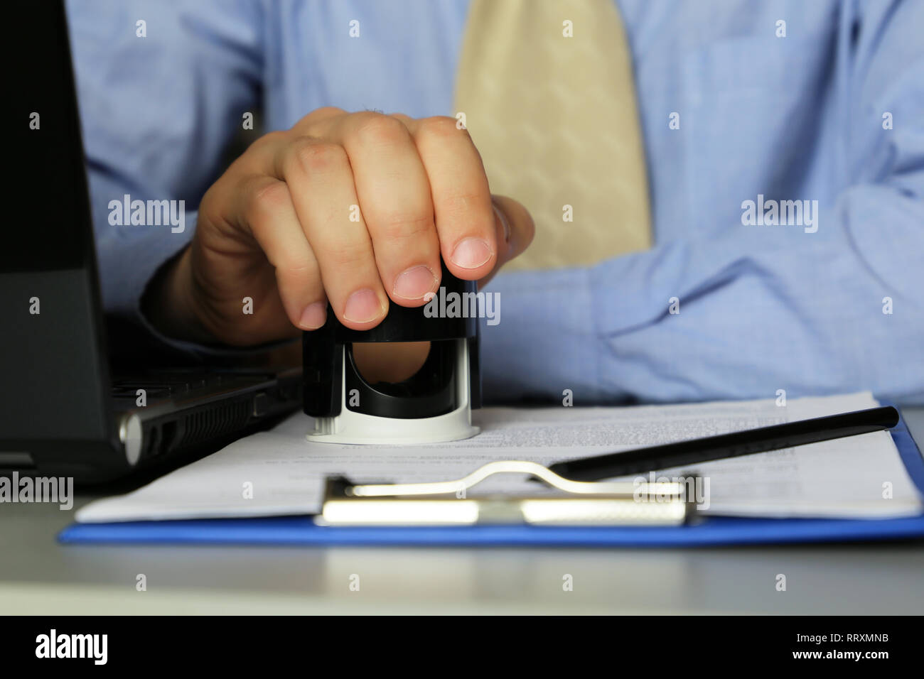 Man in business clothes puts a stamp on the documents in the office. Concept of official, manager, permission, businessman, contract - Stock Photo