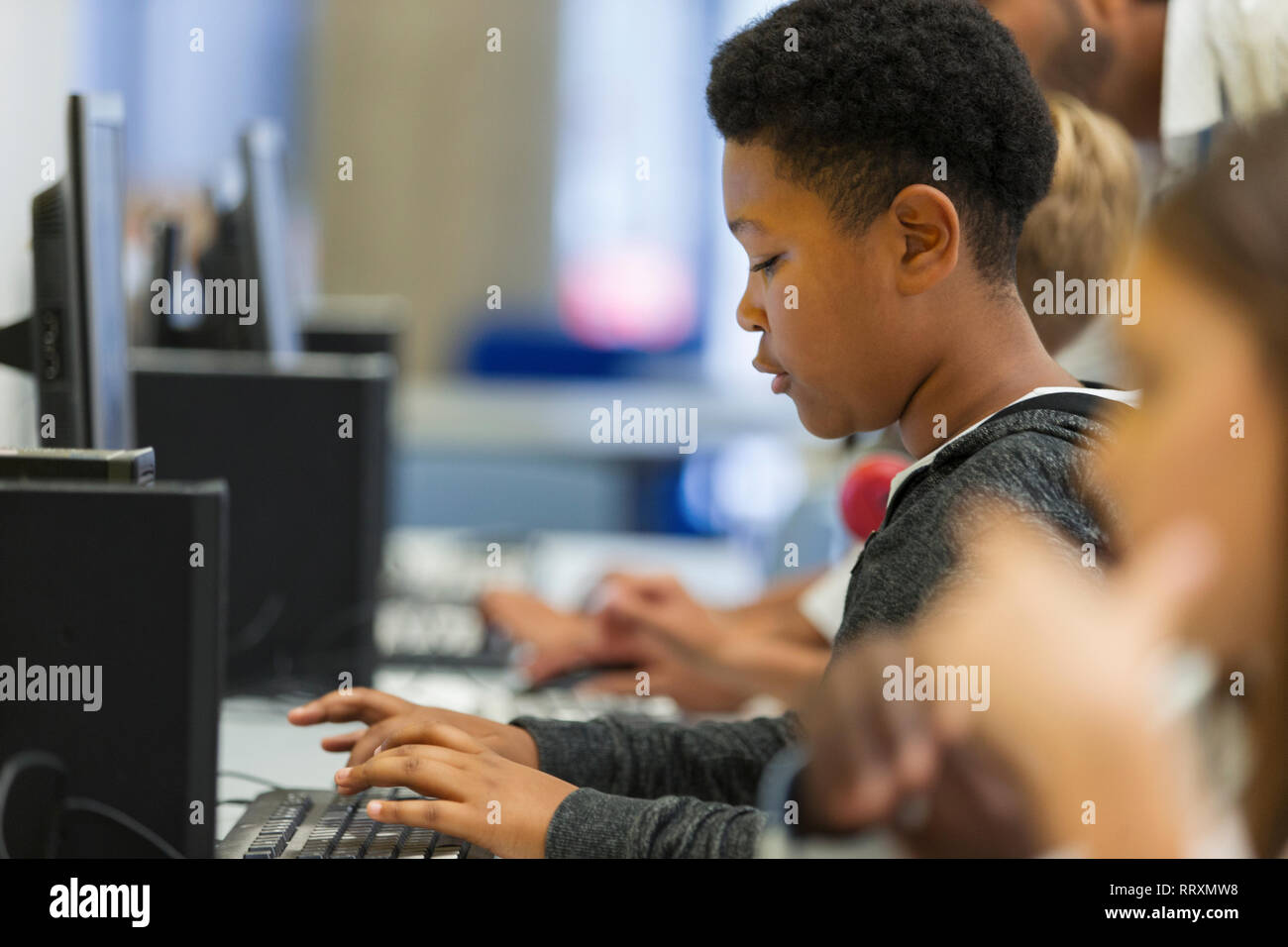 Focused junior high boy student using computer in computer lab Stock Photo