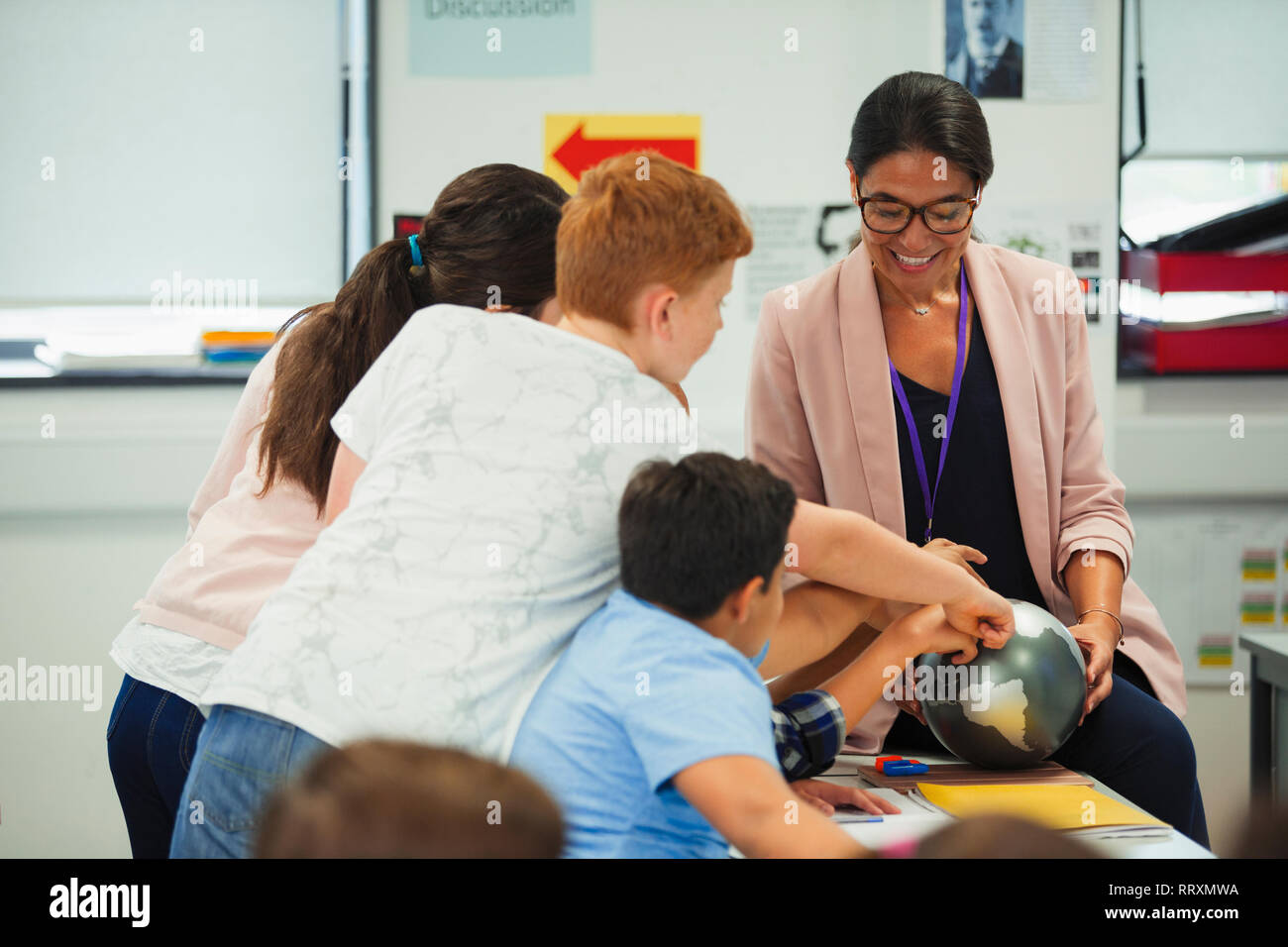 Junior high school students pointing at globe in geography teacher hands Stock Photo