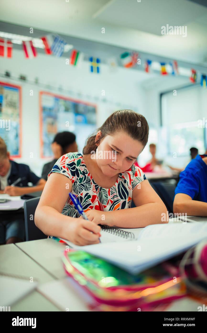 Focused junior high school girl student doing homework at desk in classroom Stock Photo