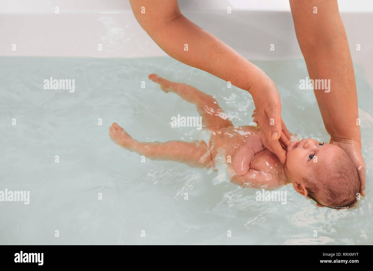 teaches infant baby to swim. Aquatic therapy for infant baby Stock Photo