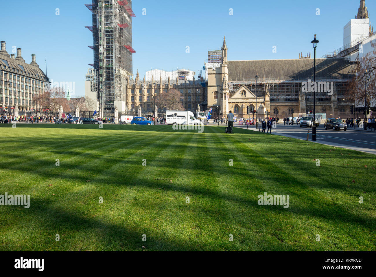 After renewing the lawn on Parliament Square, a subcontractor and landscaper cuts the lawn with a petrol lawn mower, creating an even surface of lawn. - Stock Image