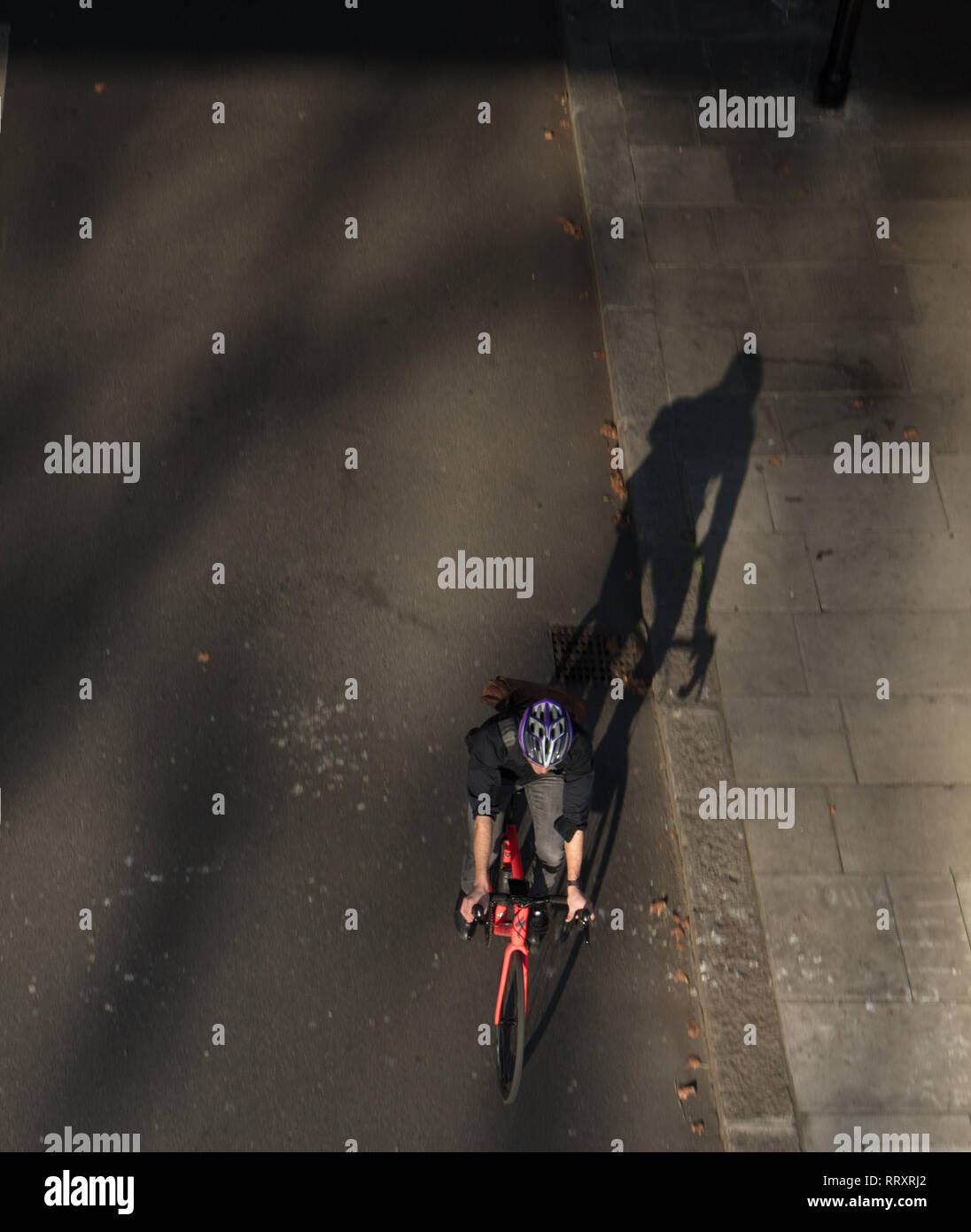 Cyclist passing under the Golden Jubilee Bridge, England, London, UK creating a long shadow on this unusual warm and spring like day in February. - Stock Image