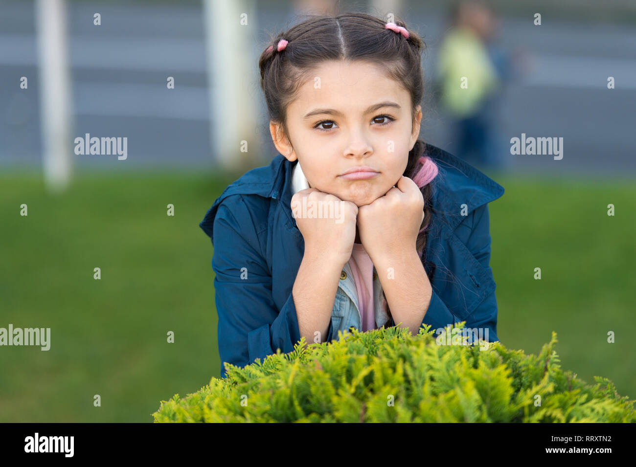 Little fashion model. Clothes and accessory. Kid wear trench coat. Spring coat. Must have concept. Fashionable coat. Girl cute face braided hair posing coat in spring park. Clothing for spring walks. - Stock Image