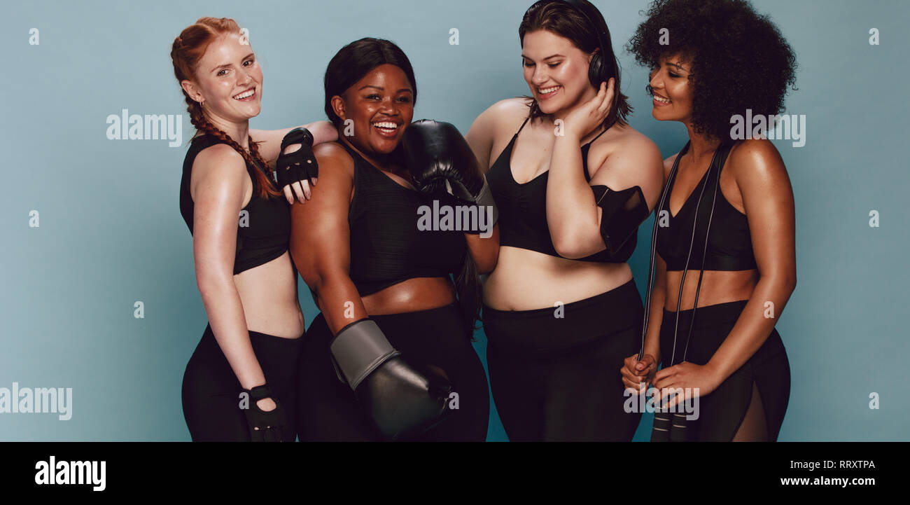 Group of women of different race and body size in sportswear standing together. Diverse women with sports equipment looking at camera against grey bac - Stock Image