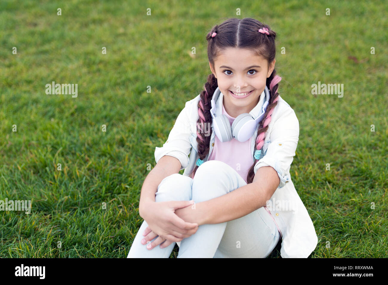 Girl braids hairstyle and modern headphones enjoy relax. Secrets to raising happy child. Girl cute kid green grass background. Healthy emotional happy kid relaxing outdoors. Get happy yourself. - Stock Image