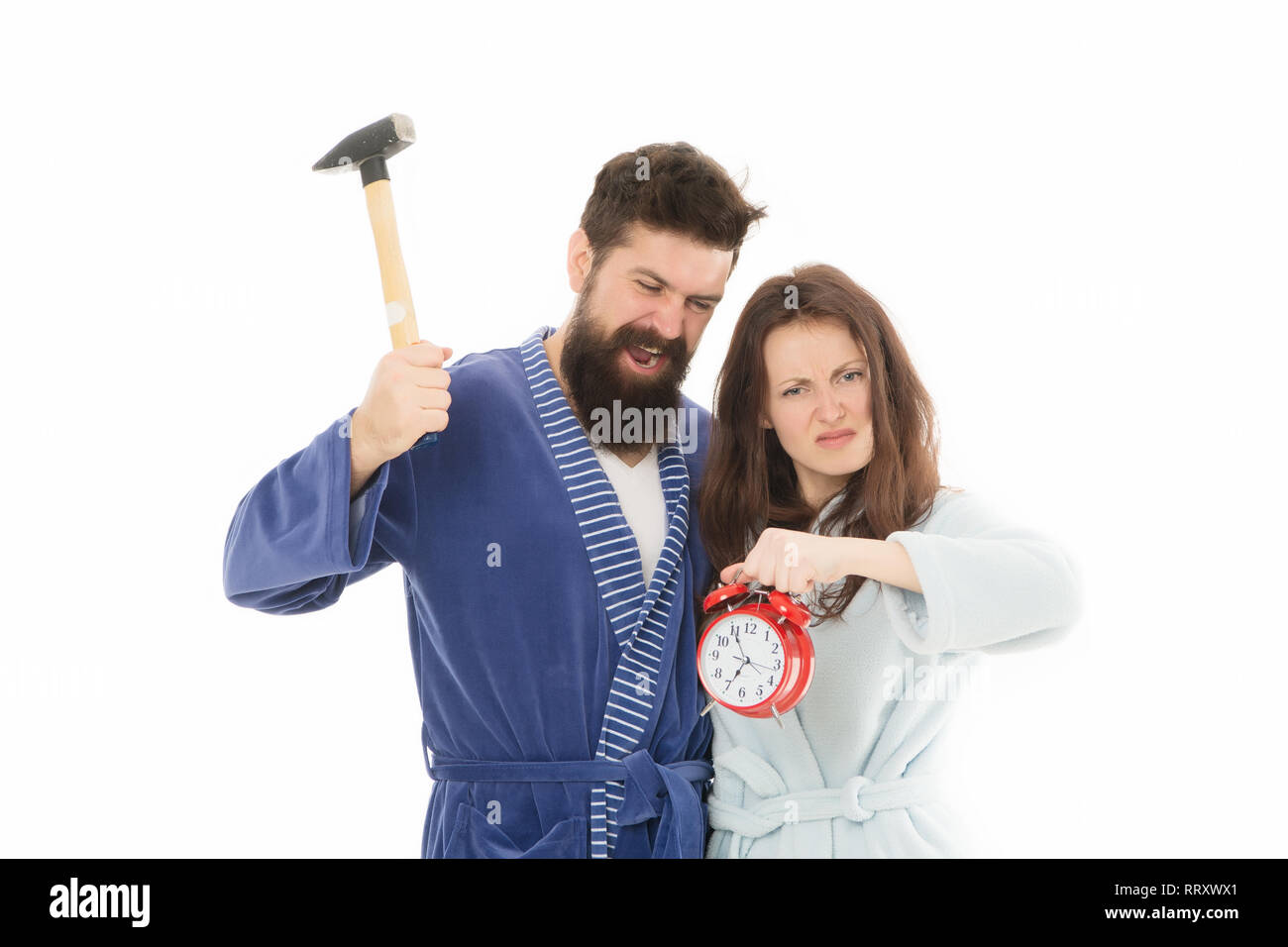 Morning tricks to set yourself up for much less stressful day. Lets get rid of this annoying alarm clock. Couple in bathrobes going to destroy alarm clock. Man hammer beat alarm clock. Hateful sound. - Stock Image