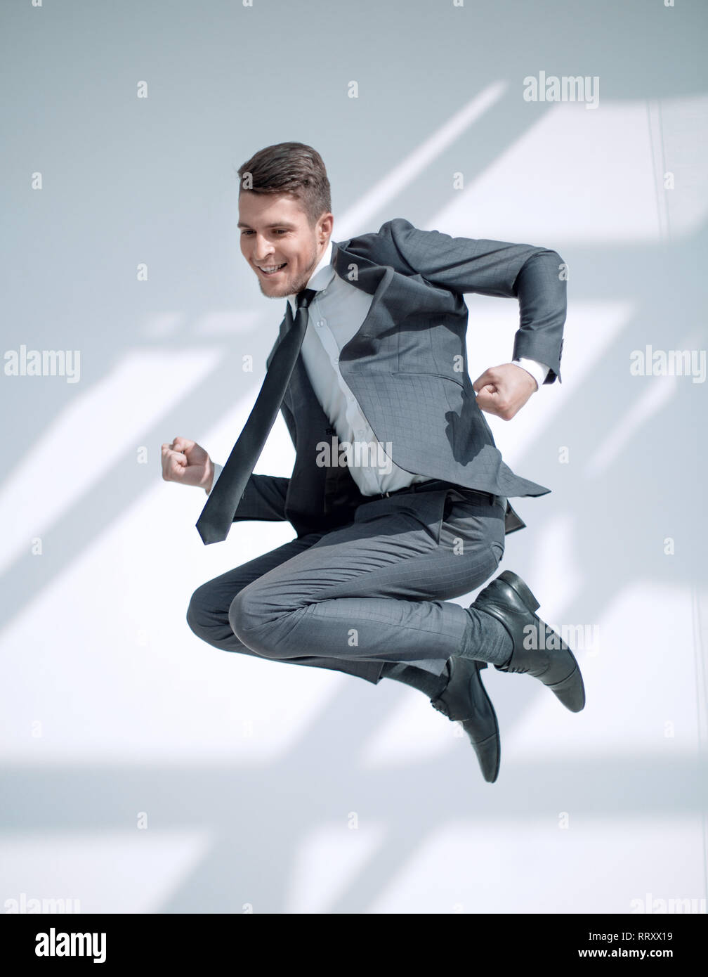Full-length jump of a young man jumping with an open mouth, isolated on a white background. - Stock Image