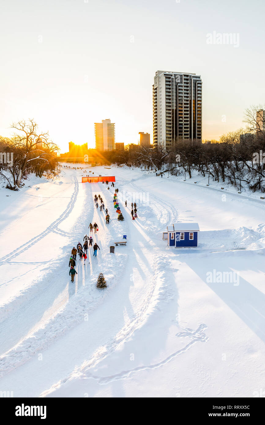 Ice skating on the Assiniboine River Trail at sunset, part of the Red River Mutual Trail, The Forks, Winnipeg, Manitoba, Canada. - Stock Image