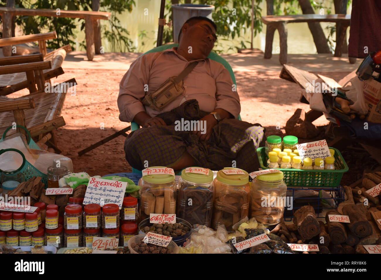 Local food vendor sleeping in his shop nearby nearby Kyauk Ka Lat pagoda in Hpa An, Myanmar - Stock Image