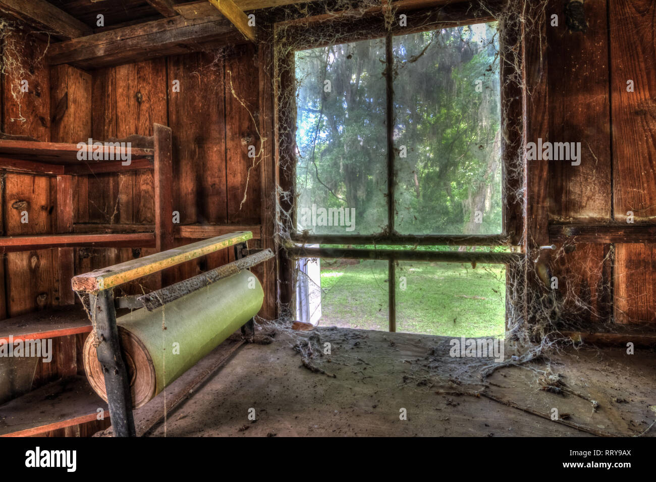 In the corner of a dusty old cobweb filled barn lies an old wooden workbench once used as a packing station. - Stock Image