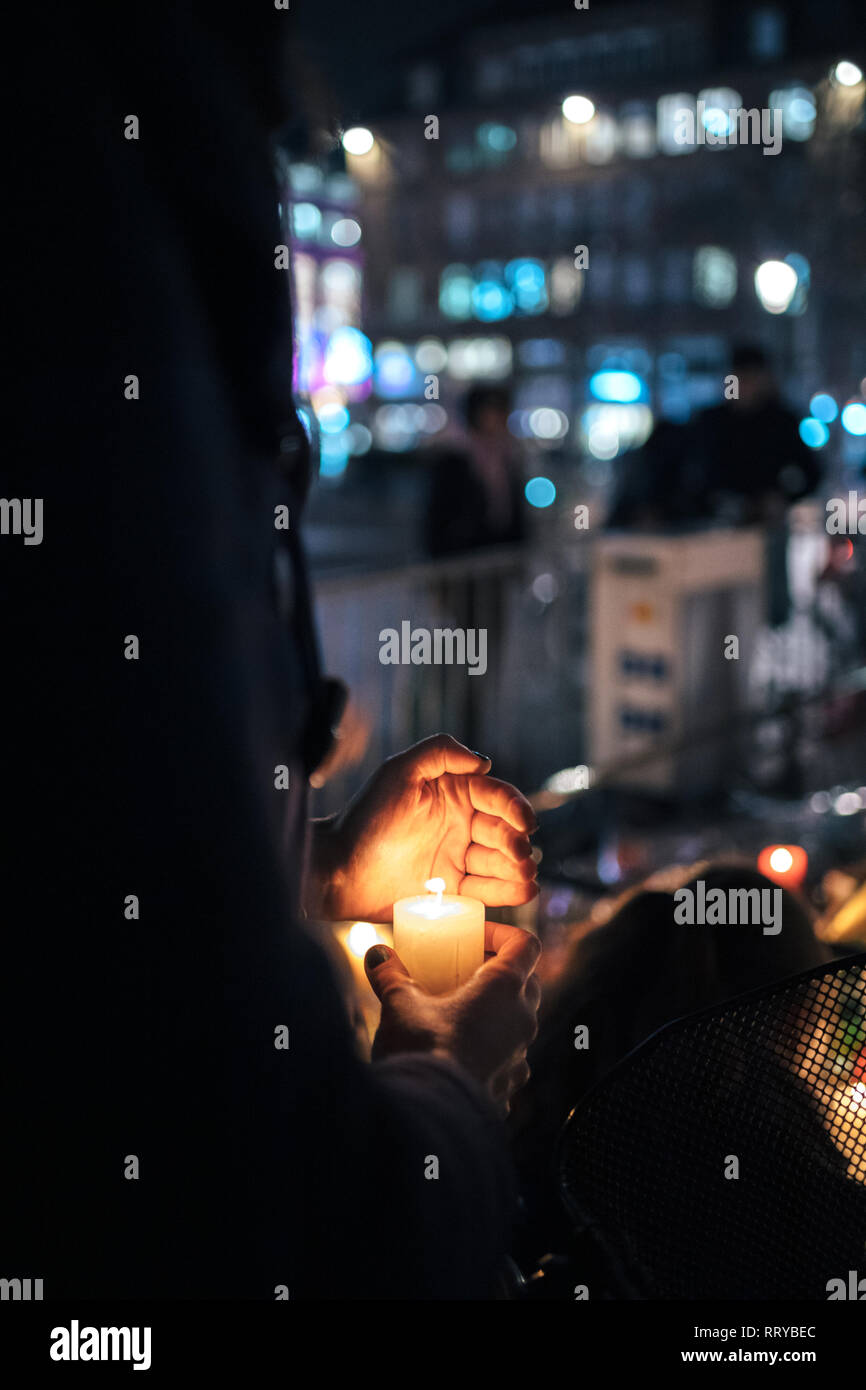 Man protecting candle frow wind in city attending a vigil with multiple light candles flowers and messages for the victims of terrorist Cherif Chekatt at Christmas Market. - Stock Image