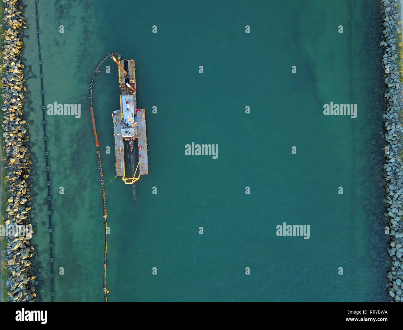 Dredging activity at sea canal from above in Queensland, Australia. The dredging aerial photography captures a bird's eye view of the engineering. - Stock Image