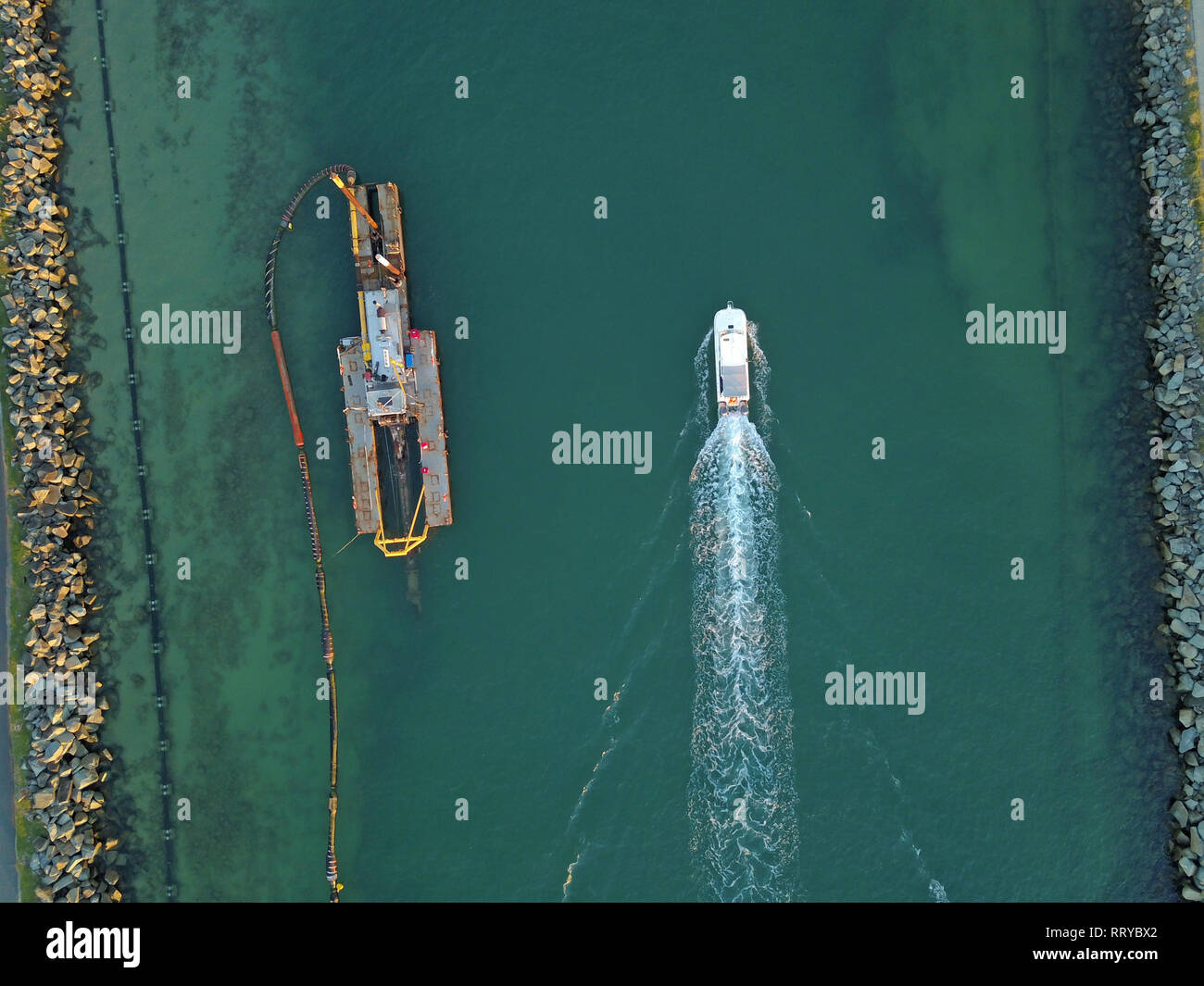 Dredging activity at sea canal from above in Queensland, Australia with speed boat with wake passing close by, and rocky shores. - Stock Image
