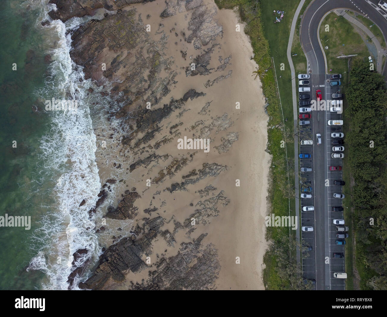 Australian car park aerial view with cars, car parking spaces, ocean and beach from above. Captured with drone photography in Queensland, Australia. - Stock Image