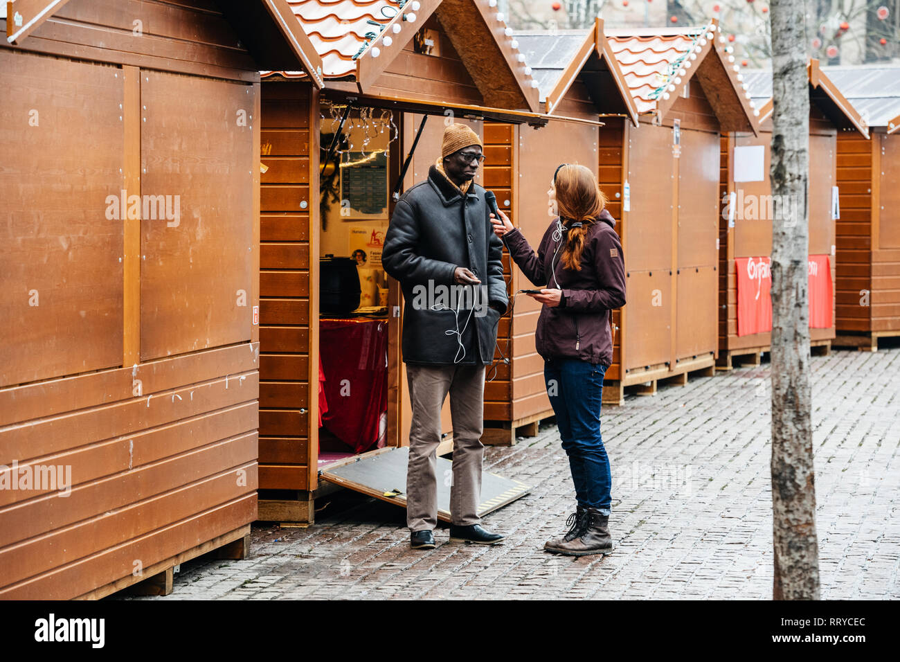 STRASBOURG, FRANCE - DEC 11, 2018: Journalist taking interview to Christmas Market seller after terrorist attack in Place Kleber - Stock Image