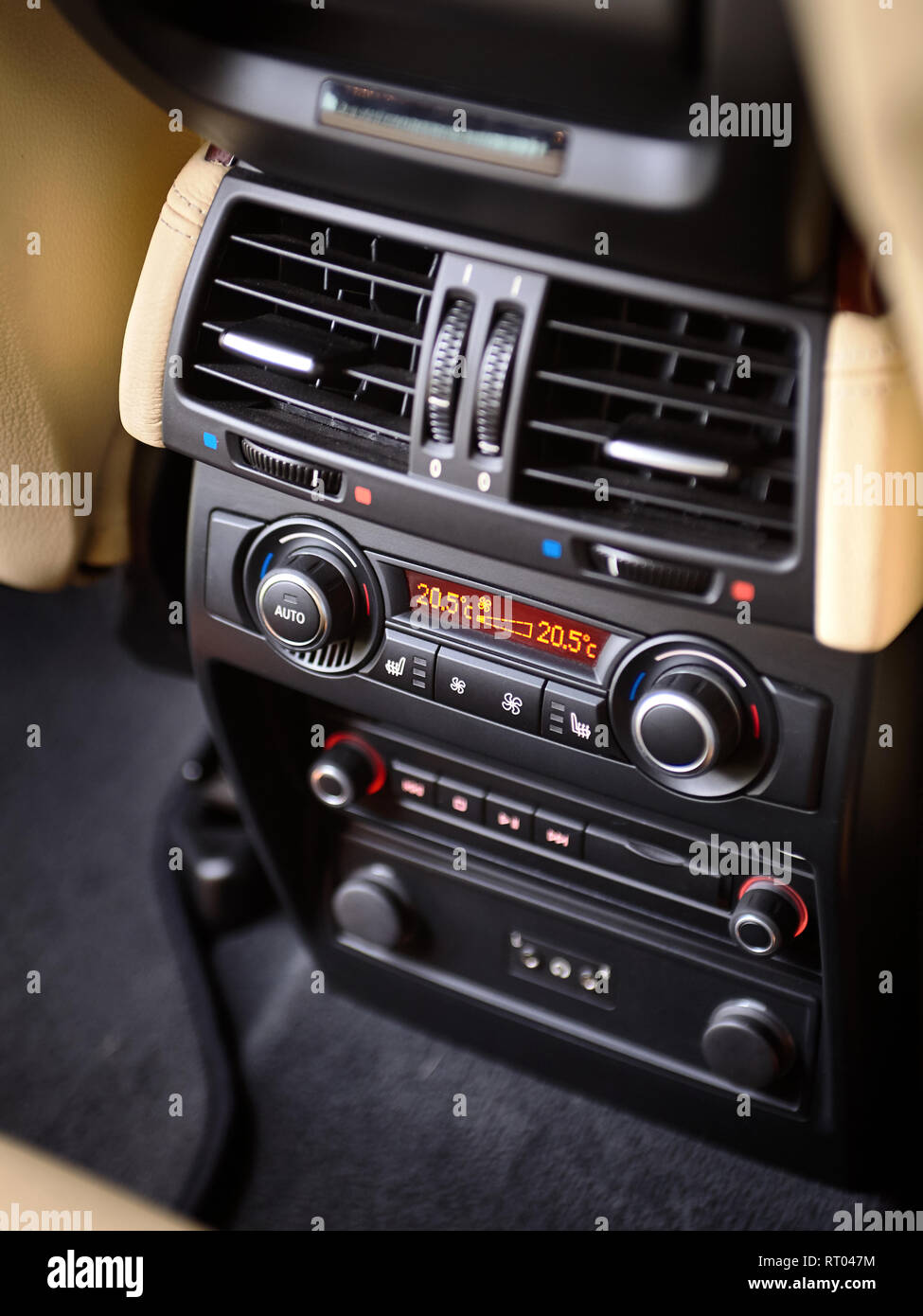 Modern car climate control panel for passengers in rear row with shallow depth of field. Four zone climate control. Car interior detail. Back passenge - Stock Image