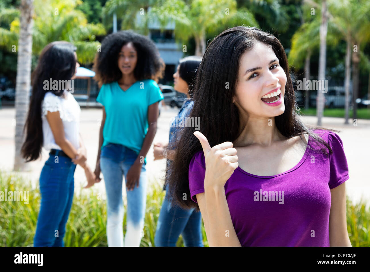 Caucasian Woman Showing Thumb With Group Of Girlfriends Outdoors In The Summer In The City