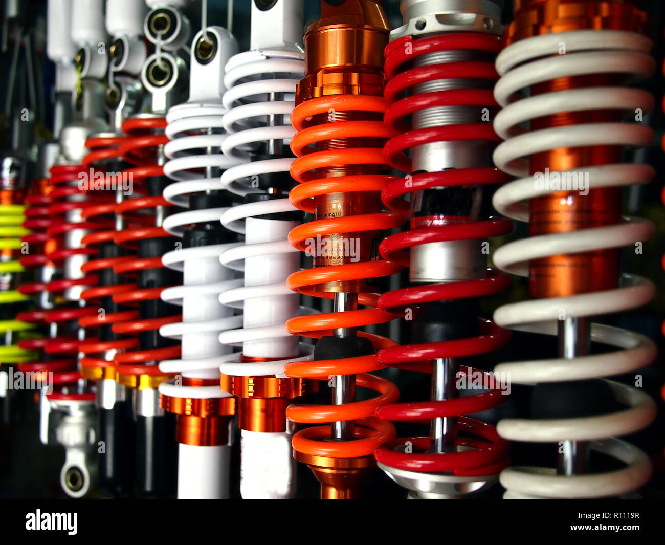 Photo of assorted colorful motorcycle shock absorbers on display at a motorcycle shop - Stock Image