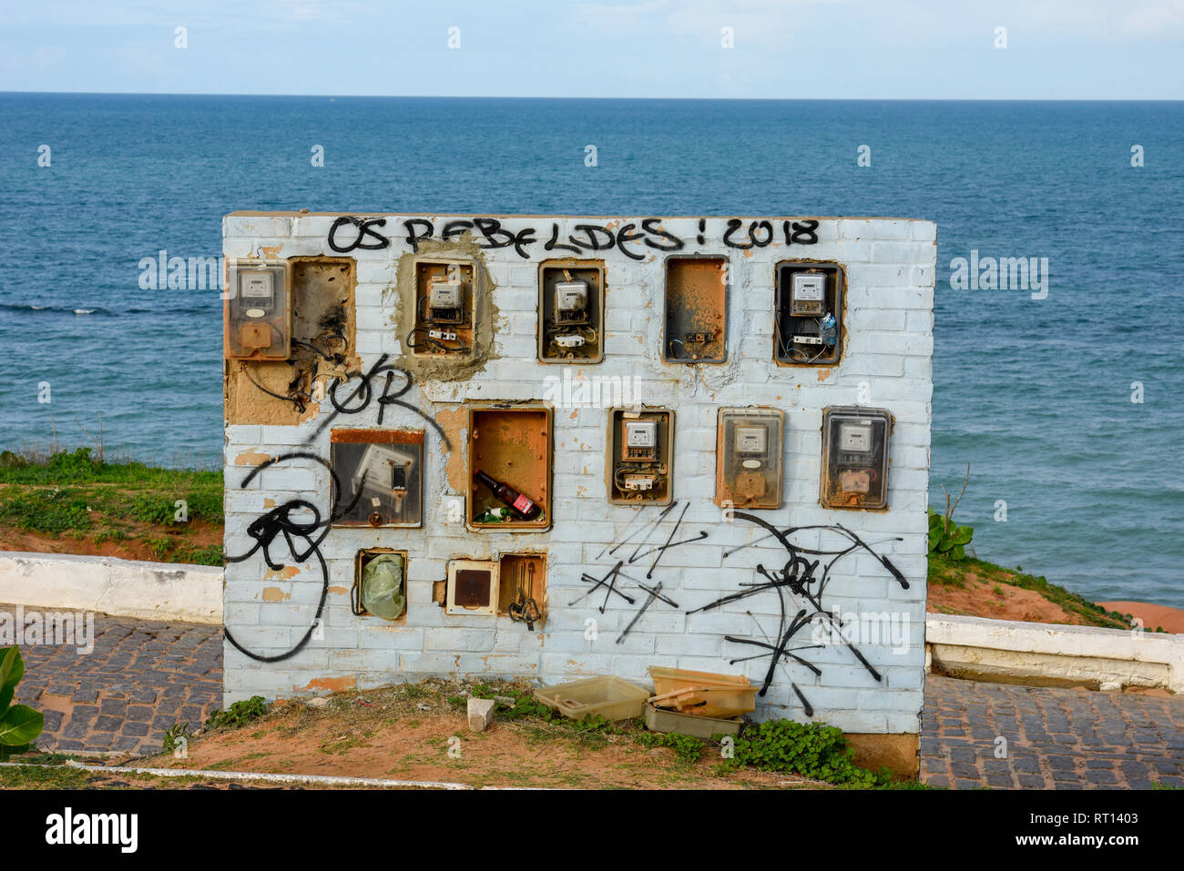 Old and broken electric meter boxes on a wall in front of the sea on Brazil Stock Photo