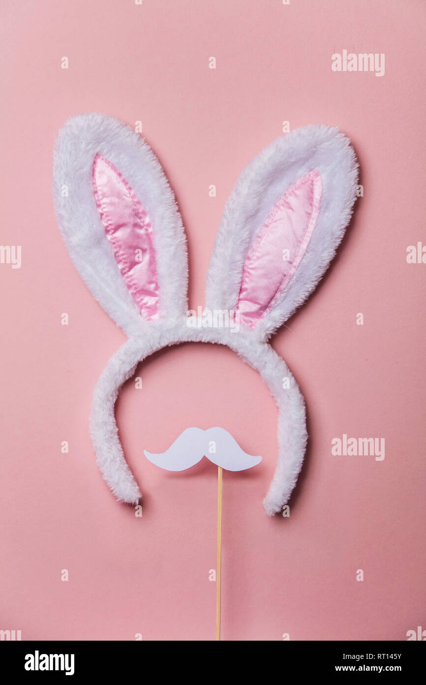 Easter bunny ears with white moustache on a pastel pink background - Stock Image
