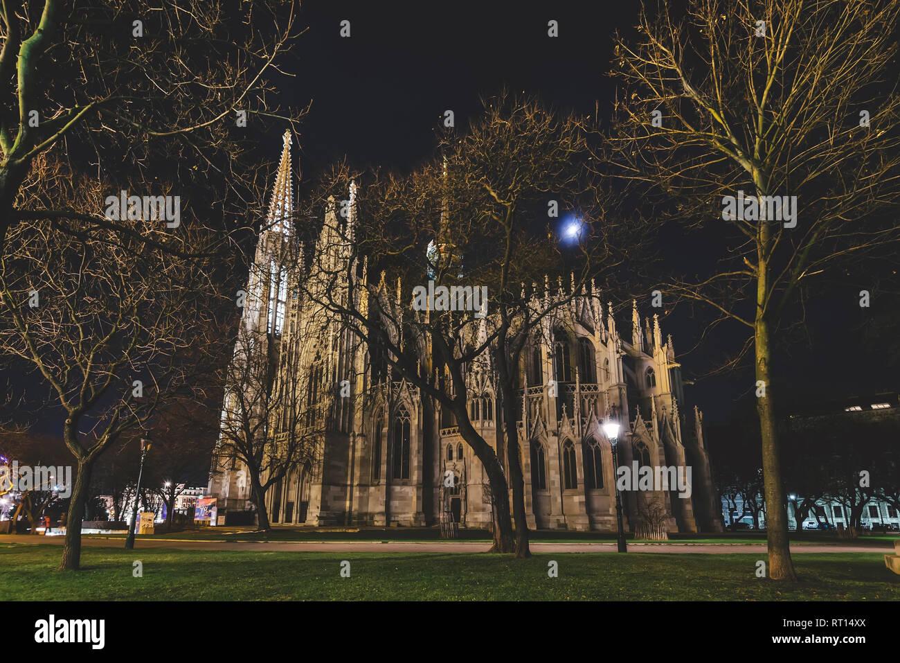 Vienna, Austria - December 25, 2017. Neo - gothic twin tower Votivkirche Illuminated at Night with no people. Facade of gothic Votive church, Sigmund  Stock Photo